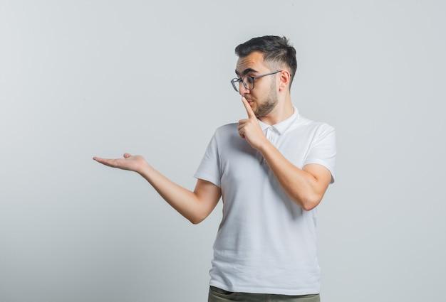 Jong mannetje dat stilte gebaar toont, palm opzij spreidt in wit t-shirt en voorzichtig kijkt