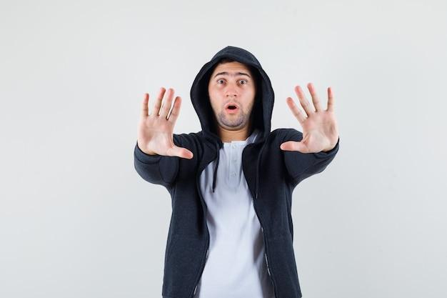 Jong mannetje dat stopgebaar in t-shirt, jasje toont en bang, vooraanzicht kijkt.
