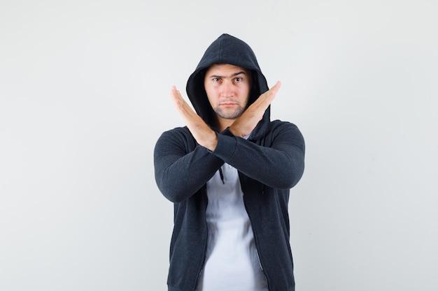 Jong mannetje dat stopgebaar in t-shirt, jasje toont en ernstig, vooraanzicht kijkt.