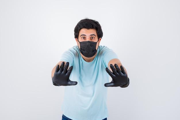 Jong mannetje dat stopgebaar in t-shirt toont en angstig kijkt. vooraanzicht.