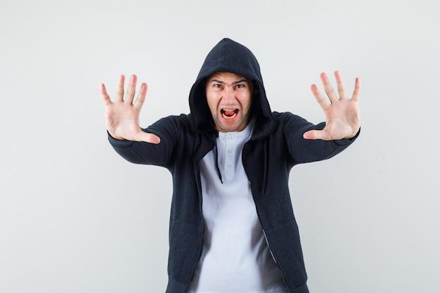 Jong mannetje dat stopgebaar toont door in t-shirt, jasje te schreeuwen en opgewonden te kijken. vooraanzicht.