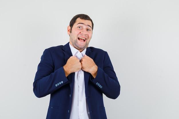 Jong mannetje dat vuisten op borst in overhemd en jasje houdt en vrolijk kijkt