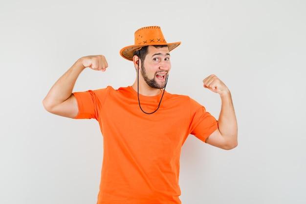 Jong mannetje dat winnaargebaar in oranje t-shirt, hoed toont en vrolijk kijkt. vooraanzicht.