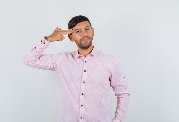 Jong mannetje dat zelfmoordgebaar maakt in roze overhemd en positief, vooraanzicht kijkt.
