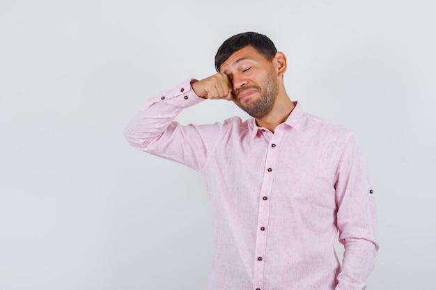 Jong mannetje dat zijn oog in roze overhemd wrijft en slaperig kijkt. vooraanzicht.