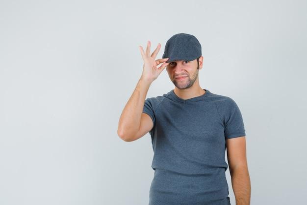 Jong mannetje dat zijn pet in grijs t-shirt houdt en elegant kijkt