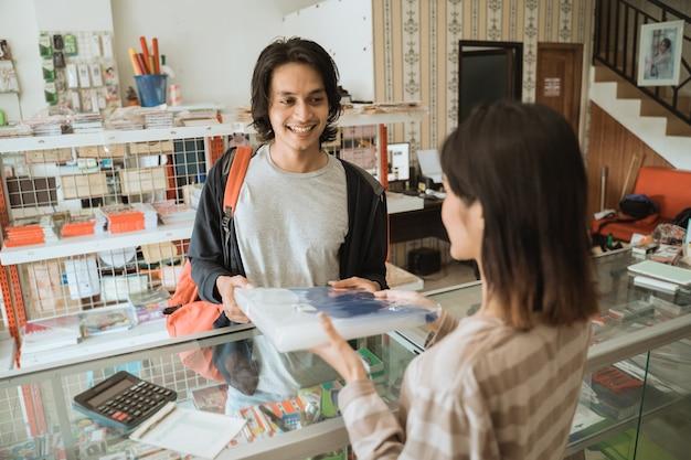 Jong mannetje die een kantoorbehoeftenwinkel bezoeken die briefpapier kopen