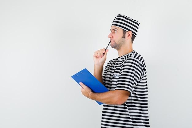 Jong mannetje holdingsklembord, pen in t-shirt, hoed en nadenkend kijkt.