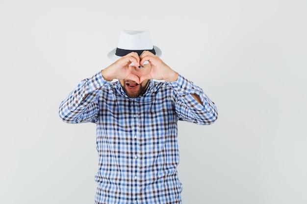 Jong mannetje in geruit overhemd, hoed die hartgebaar toont en optimistisch, vooraanzicht kijkt.