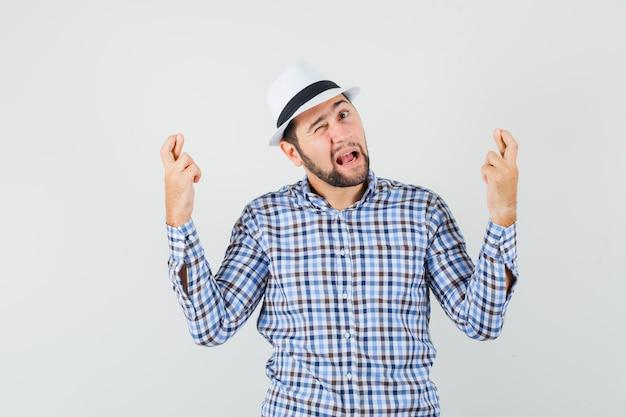 Jong mannetje in geruit overhemd, hoed die vingers gekruist houdt, mond opent, knipoogend oog, vooraanzicht.