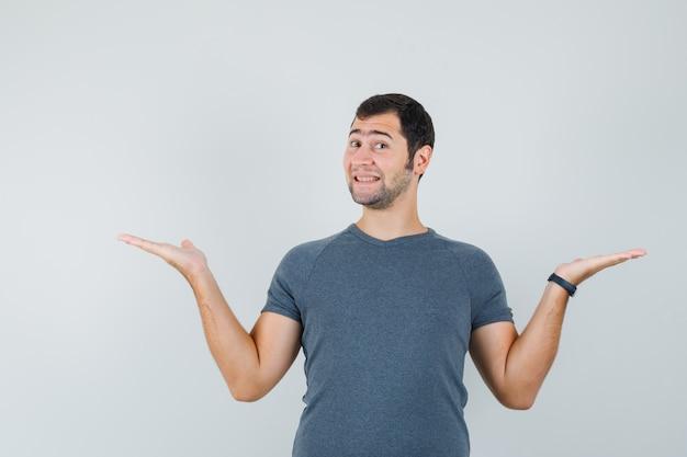 Jong mannetje in grijs t-shirt dat iets vergelijkt of toont en vrolijk kijkt