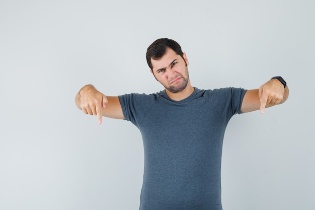 Jong mannetje in grijs t-shirt dat naar beneden wijst en somber kijkt