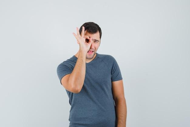 Jong mannetje in grijs t-shirt dat ok teken op oog toont en nieuwsgierig kijkt