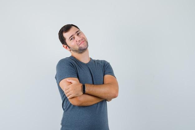 Jong mannetje in grijs t-shirt dat zich met gekruiste wapens bevindt en positief kijkt