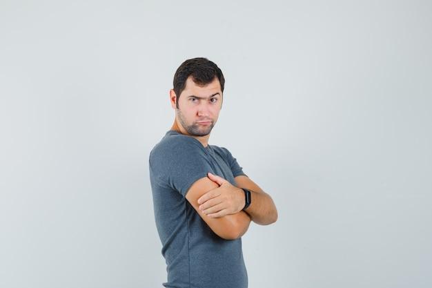 Jong mannetje in grijs t-shirt dat zich met gekruiste wapens bevindt en twijfelachtig kijkt