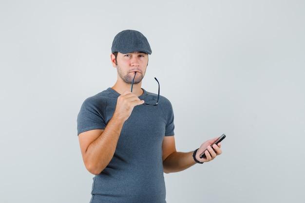 Jong mannetje in grijs t-shirtglb die glazen bijten die mobiele telefoon houden en peinzend kijken