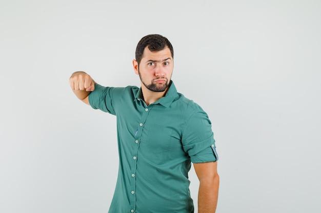 Jong mannetje in groen overhemd dat zijn vuist op agressieve manier toont en woedend kijkt, vooraanzicht.