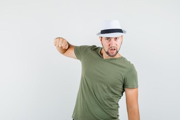 Jong mannetje in groen t-shirt en hoed die met vuist bedreigen en zenuwachtig kijken