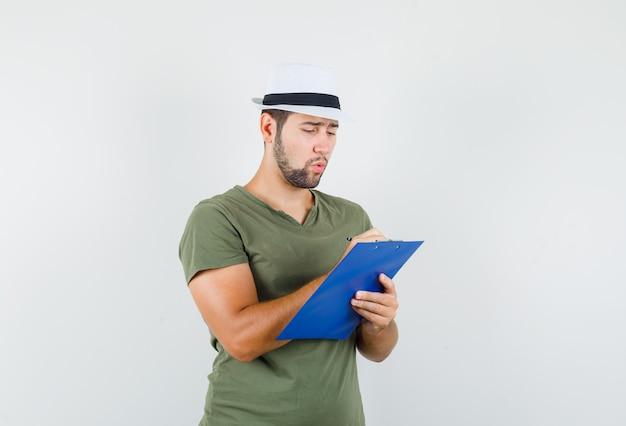 Jong mannetje in groen t-shirt en hoed die nota's op klembord maakt en bezig kijkt