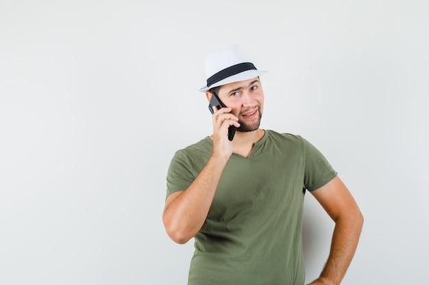 Jong mannetje in groen t-shirt en hoed die op mobiele telefoon spreken en glimlachen