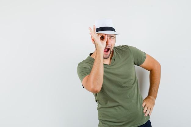 Jong mannetje in groen t-shirt en hoed, jeans die ok teken op oog tonen en grappig kijken