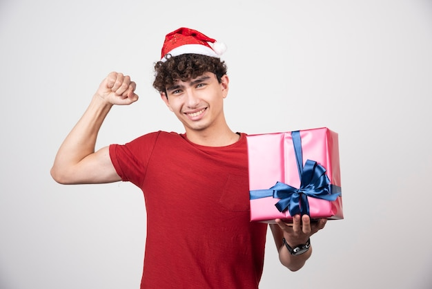 Jong mannetje in kerstmanhoed die zijn spieren toont.