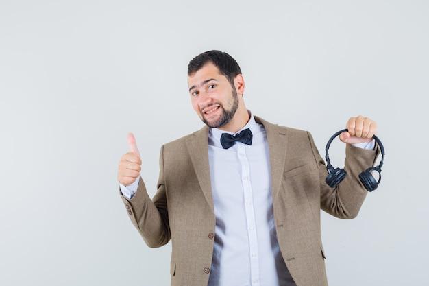 Jong mannetje in kostuum die hoofdtelefoons met omhoog houden en vrolijk, vooraanzicht kijken.