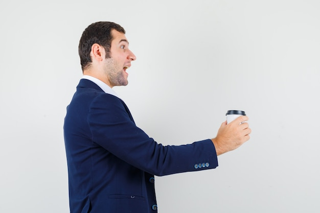 Jong mannetje in overhemd en jasje die kop van koffie aanbieden en vrolijk kijken