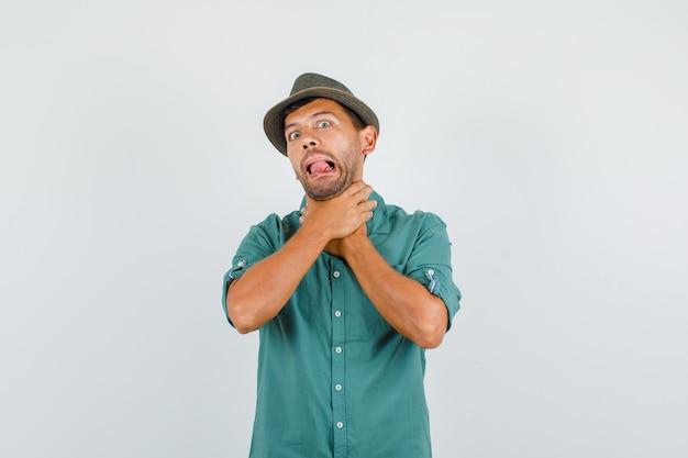 Jong mannetje in overhemd, hoed die probeert te wurgen en grappig kijkt