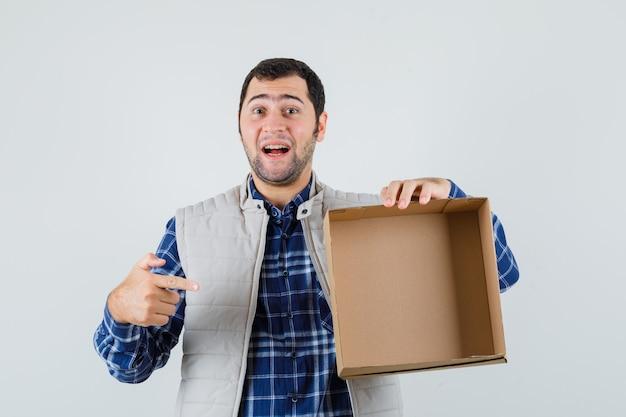 Jong mannetje in overhemd, jasje wijst naar lege doos, vooraanzicht.