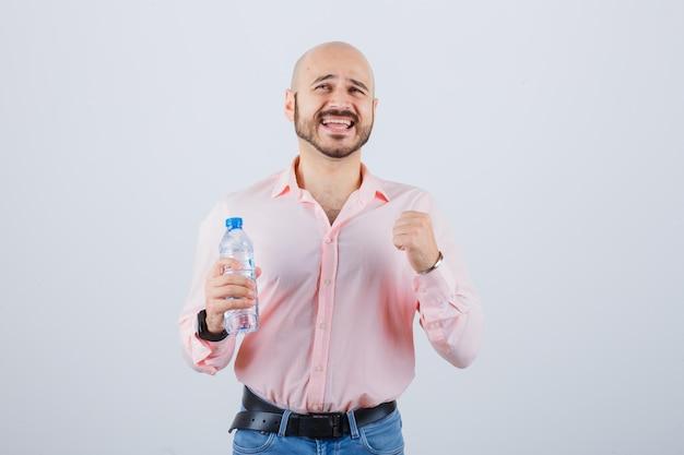 Jong mannetje in overhemd, jeans die winnaargebaar tonen en gelukkig kijken, vooraanzicht.