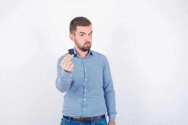 Jong mannetje in overhemd, spijkerbroek die lichter houdt en zelfverzekerd kijkt, vooraanzicht.