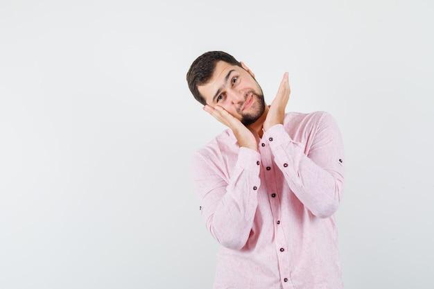Jong mannetje in roze overhemd leunende wang op opgeheven palm en ziet er schattig uit