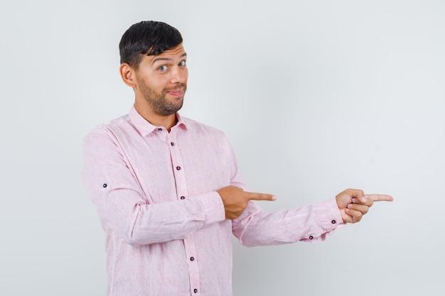 Jong mannetje in roze overhemd wijst naar kant en kijkt vrolijk, vooraanzicht.