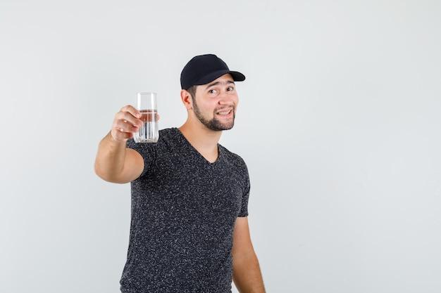 Jong mannetje in t-shirt en pet die glas water aanbiedt en er vriendelijk uitziet