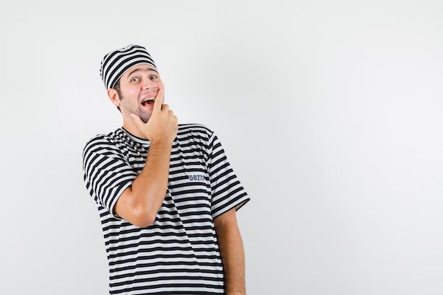 Jong mannetje in t-shirt, hoed die hand op mond houdt en vrolijk, vooraanzicht kijkt.
