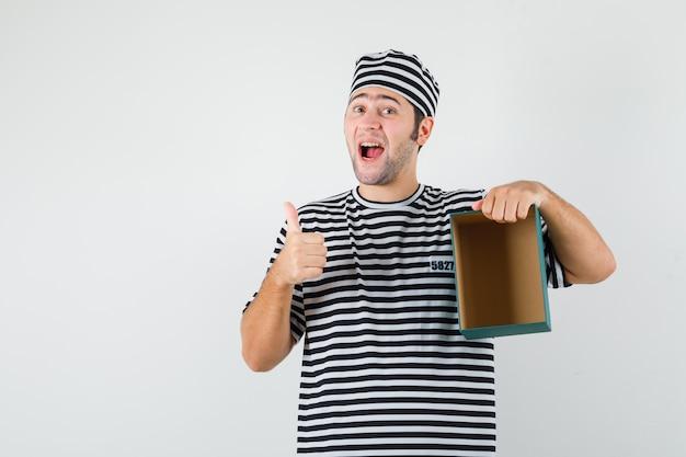 Jong mannetje in t-shirt, hoed die lege giftdoos houdt, duim toont en gelukkig, vooraanzicht kijkt.