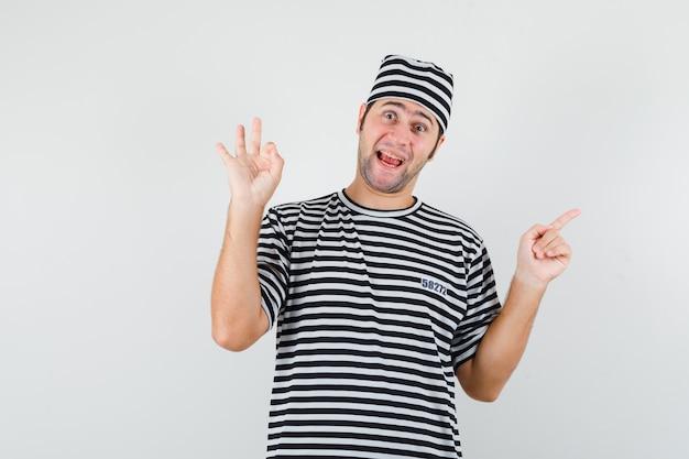 Jong mannetje in t-shirt, hoed die ok gebaar toont, opzij wijst en vrolijk, vooraanzicht kijkt.