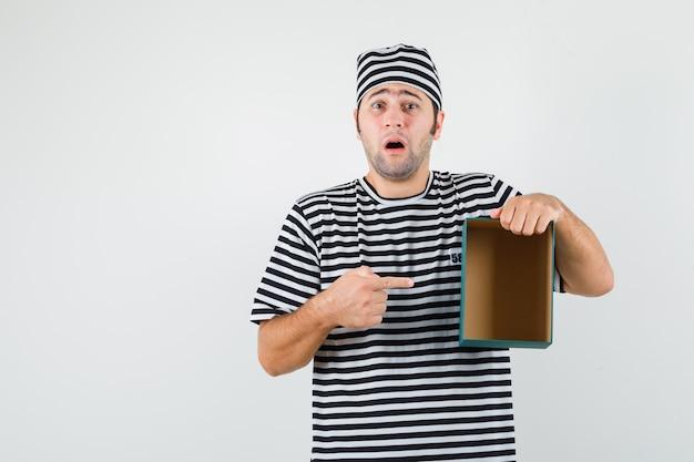 Jong mannetje in t-shirt, hoed die op lege giftdoos richt en verdrietig, vooraanzicht kijkt.