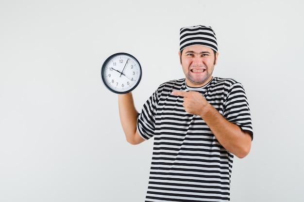 Jong mannetje in t-shirt, hoed die op muurklok richt en vrolijk, vooraanzicht kijkt.