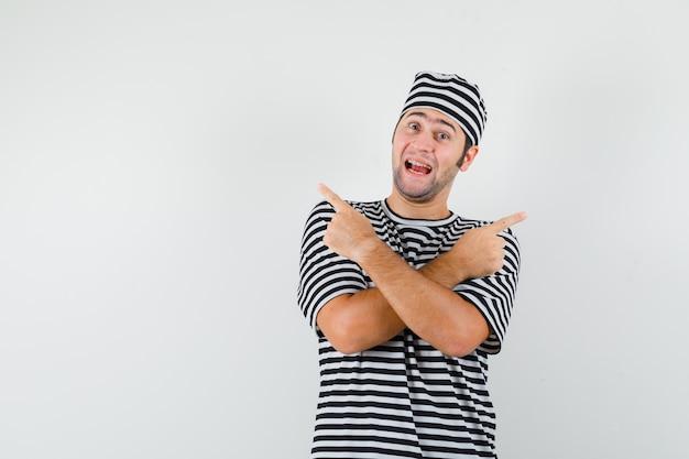 Jong mannetje in t-shirt, hoed die weg wijst en vrolijk, vooraanzicht kijkt.