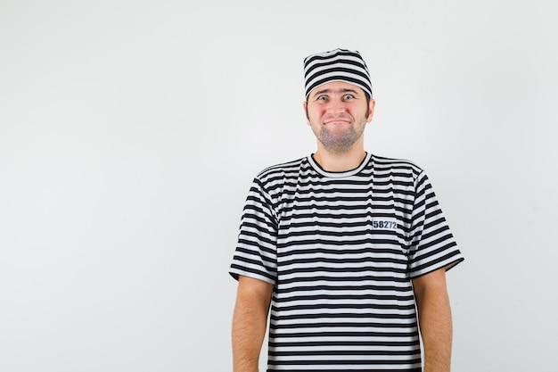 Jong mannetje in t-shirt, hoed en op zoek grappig. vooraanzicht.