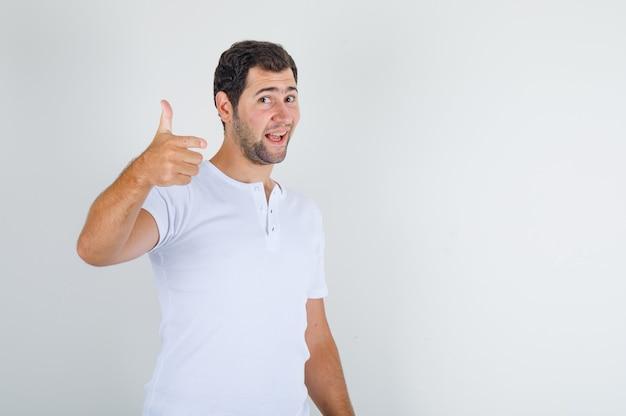 Jong mannetje in wit t-shirt dat duim toont en tevreden glimlacht kijkt