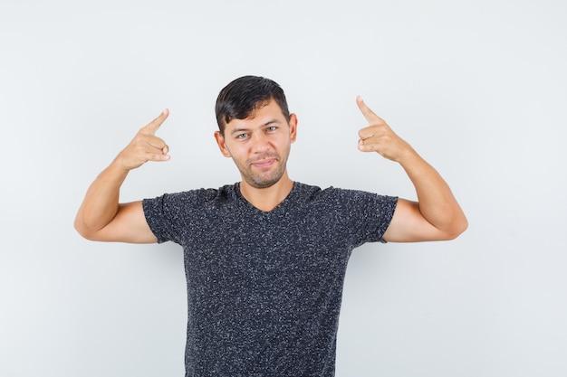 Jong mannetje in zwart t-shirt dat en tevreden, vooraanzicht benadrukt kijkt.
