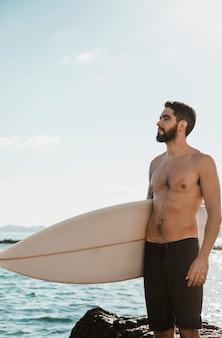 Jong mannetje met surfplank in de buurt van zee