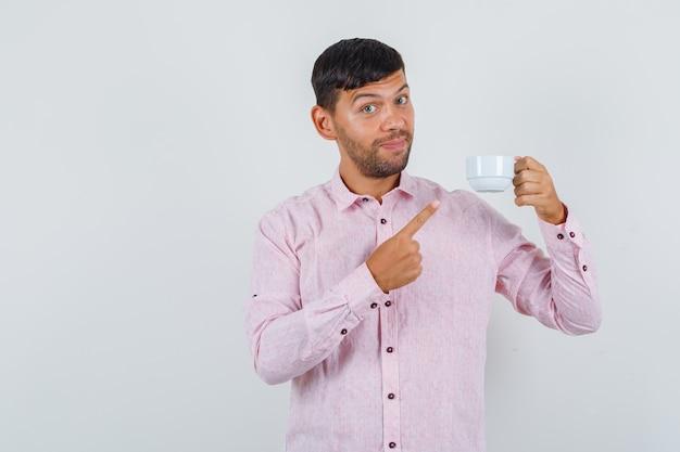 Jong mannetje wijzend op kopje thee en lachend in roze shirt vooraanzicht.