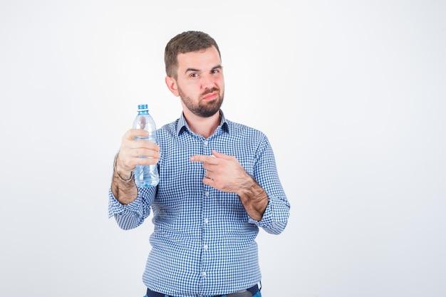 Jong mannetje wijzend op plastic waterfles in shirt, spijkerbroek en kijkt zelfverzekerd, vooraanzicht.