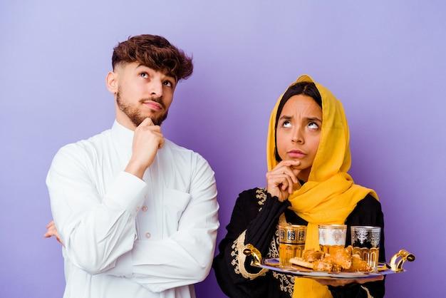 Jong marokkaans koppel dat thee drinkt die ramadan-maand vieren die op purpere muur wordt geïsoleerd