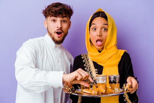 Jong marokkaans koppel het drinken van thee vieren ramadan maand geïsoleerd op paars