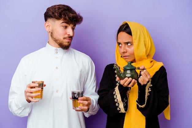 Jong marokkaans koppel het drinken van thee vieren ramadan maand geïsoleerd op paarse achtergrond